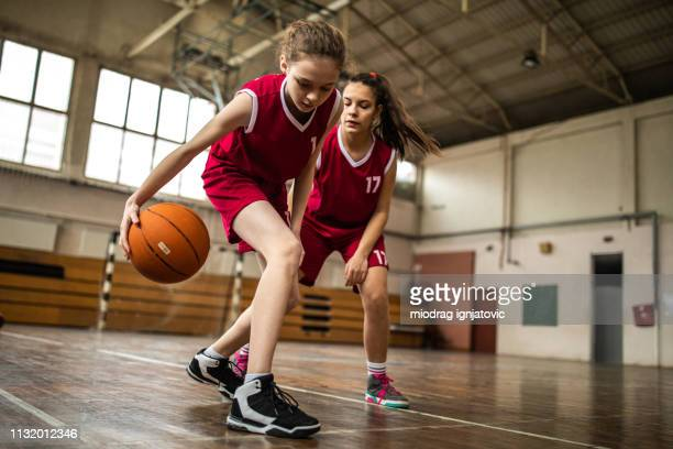 teenage girls playing basketball - charging sports stock pictures, royalty-free photos & images