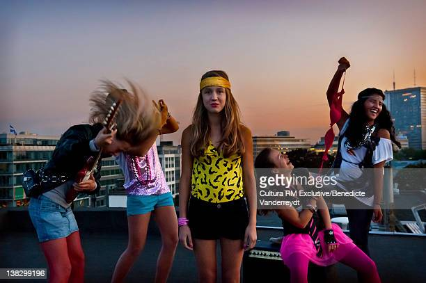 Teenage girls playing music on roof