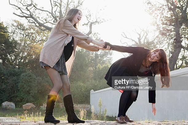 Teenage girls playing on stone wall