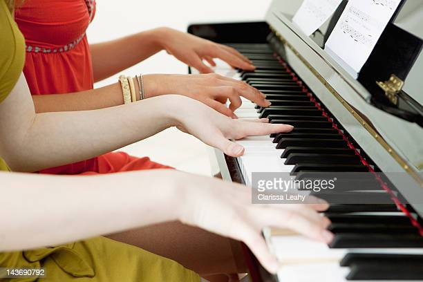 teenage girls playing piano together - duet stock pictures, royalty-free photos & images