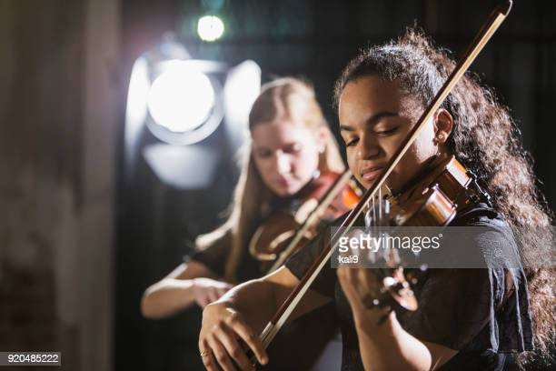 Teenage girls playing violin in concert