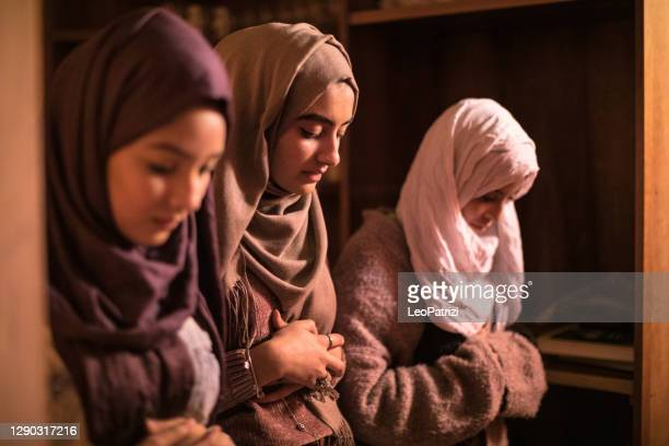 teenage girls praying in a mosque - religious celebration stock pictures, royalty-free photos & images