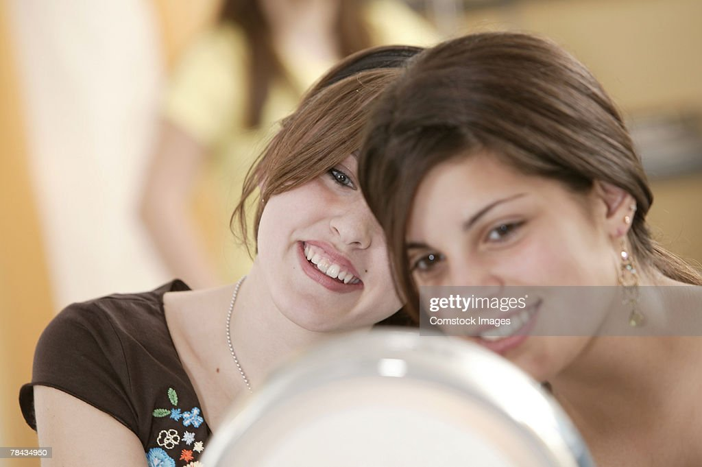 Teenage girls primping themselves with a mirror : Stockfoto