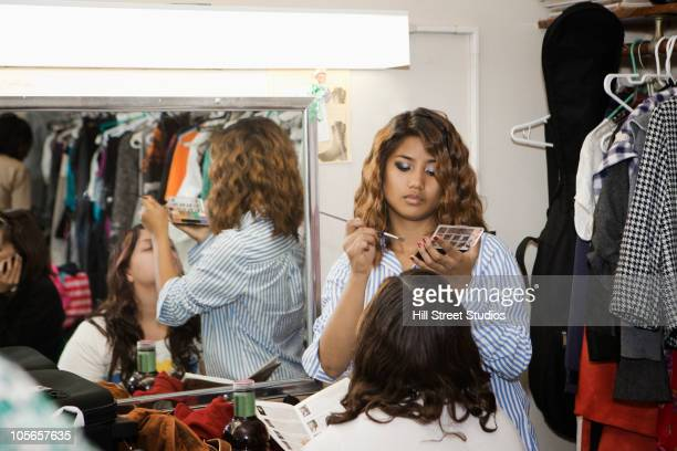 Teenage girls putting makeup on backstage
