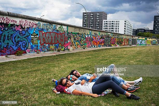 Teenage girls relax in the park alongside the former Berlin Wall at 'East Side Gallery' in Berlin At Midnight on November 9th East Germany's...