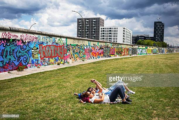Teenage girls relax in the park alongside the former Berlin Wall at 'East Side Gallery' in Berlin In the background are the logo and offices of...