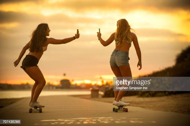 Teenage girls riding skateboards holding cell phones