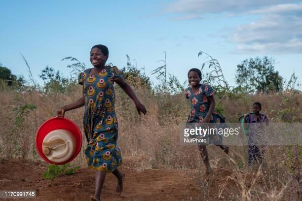 Teenage girls run to a water well in Kwatula Village Malawi on 17 June 2017