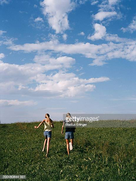 teenage girls (12-18) running across field, rear view - blasius erlinger stock pictures, royalty-free photos & images