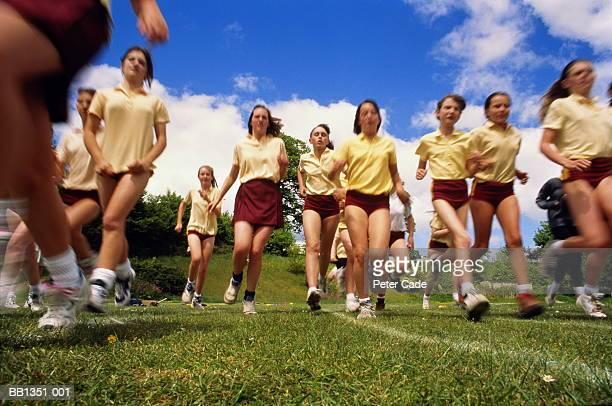 Teenage girls running race on school sports field, low angle
