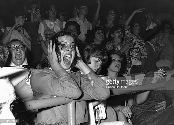 Teenage girls scream during a Beatles concert in 1964