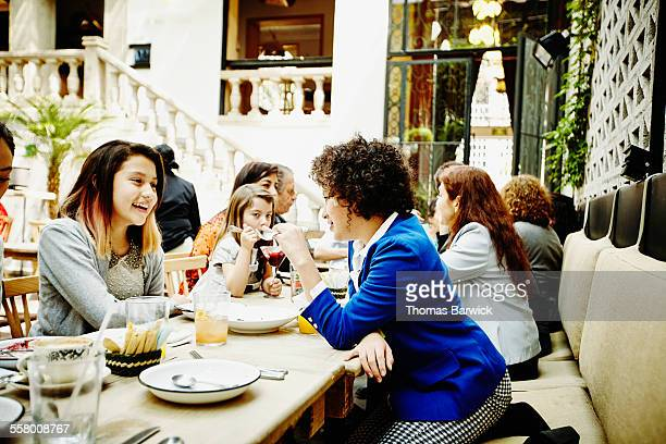 Teenage girls sharing dessert during family dinner