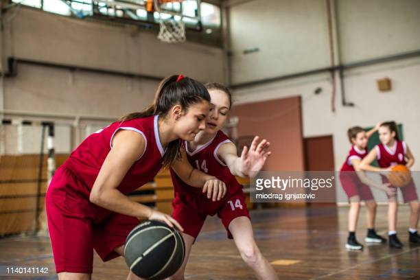 teenage girls showing skills at basketball match - charging sports stock pictures, royalty-free photos & images
