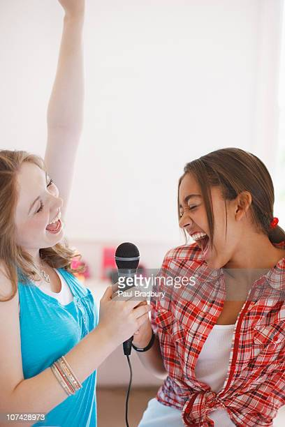 teenage girls singing into microphone - duet stock pictures, royalty-free photos & images