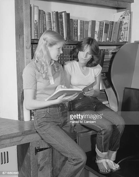 teenage girls sitting and reading book in library - {{ collectponotification.cta }} foto e immagini stock