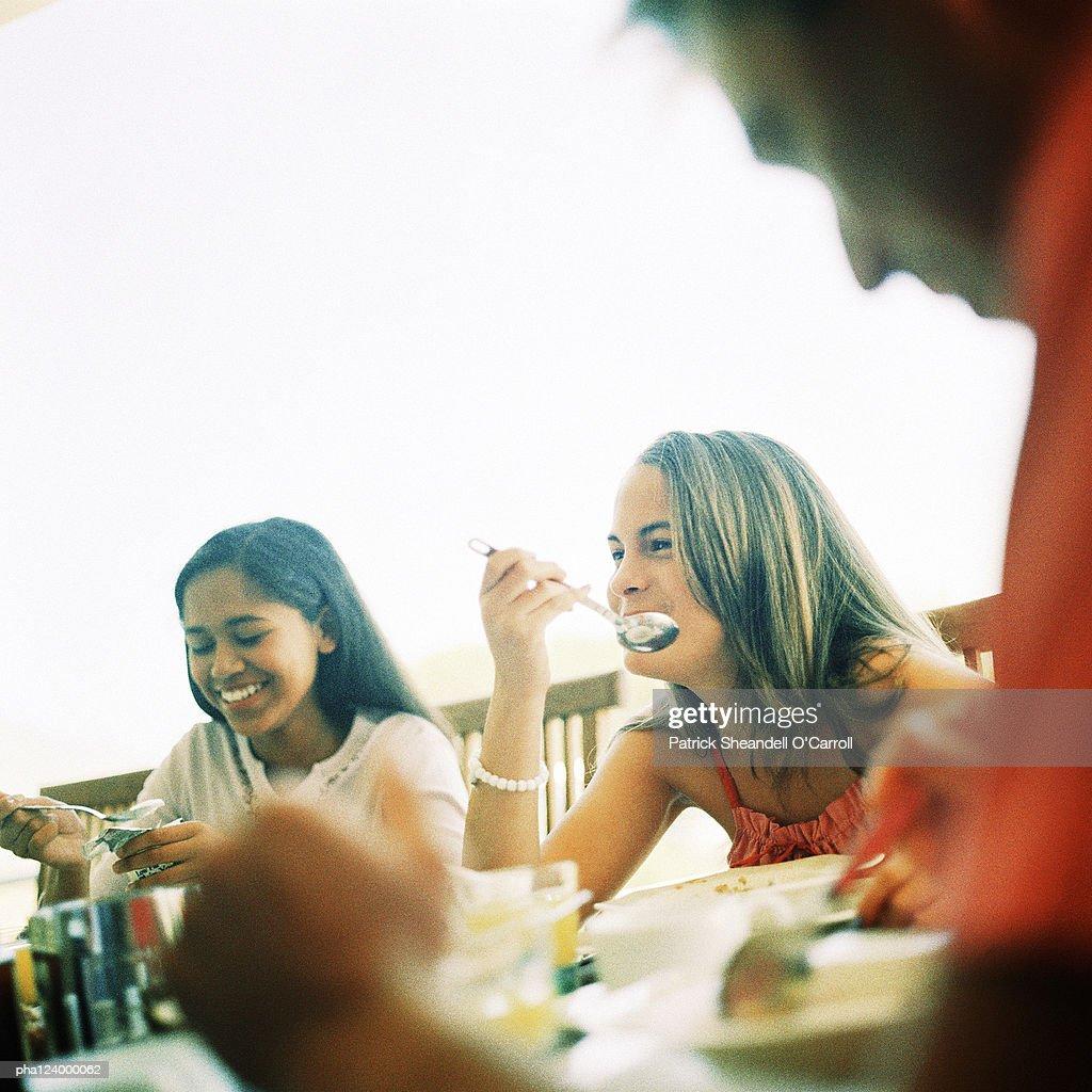 Teenage girls sitting at table, smiling : Stockfoto