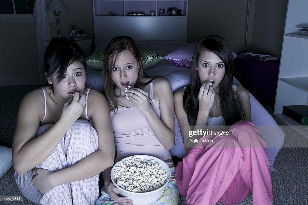 Teenage girls sitting in a bedroom eating popcorn : Foto de stock