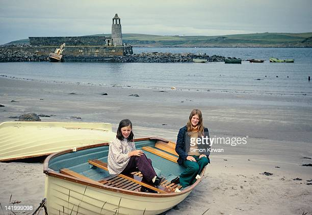 teenage girls sitting in boat on beach - two objects stock pictures, royalty-free photos & images