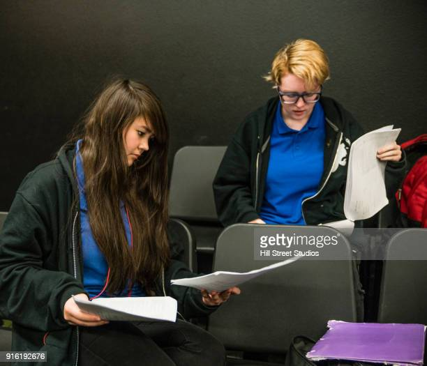 Teenage girls sitting in chairs reading scripts