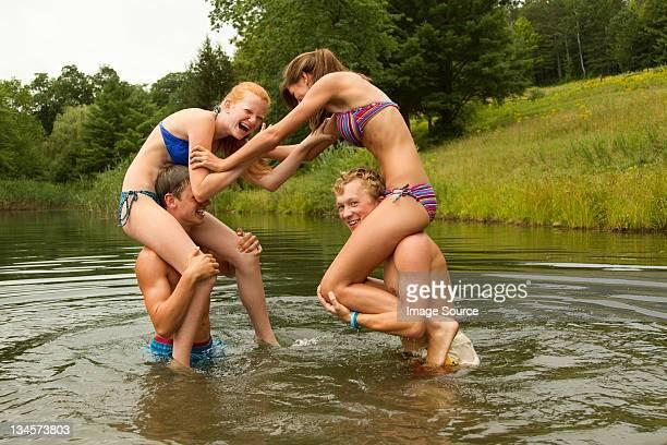 Teenage girls sitting on boys' shoulders in lake