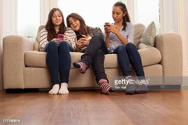 Jeunes filles assis sur un canapé à regarder téléphones