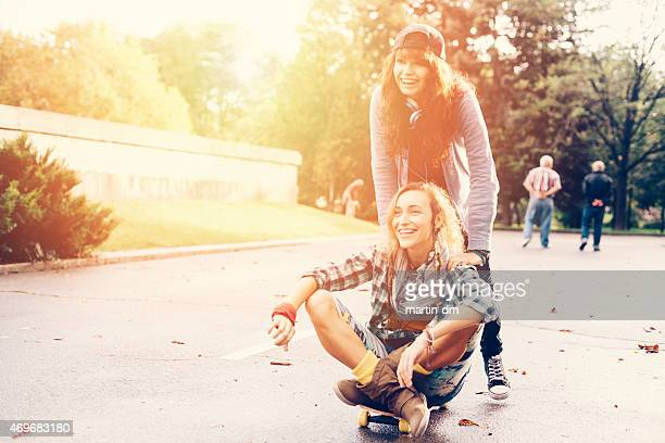 Teenage girls skateboarding in the city park