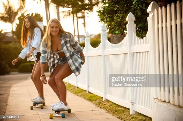 Teenage girls skateboarding on sidewalk