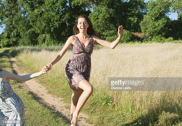 Teenage girls skipping on dirt path