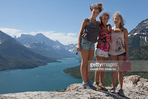 teenage girls stand on rock summit, lake & mtns - hot pants stock photos and pictures