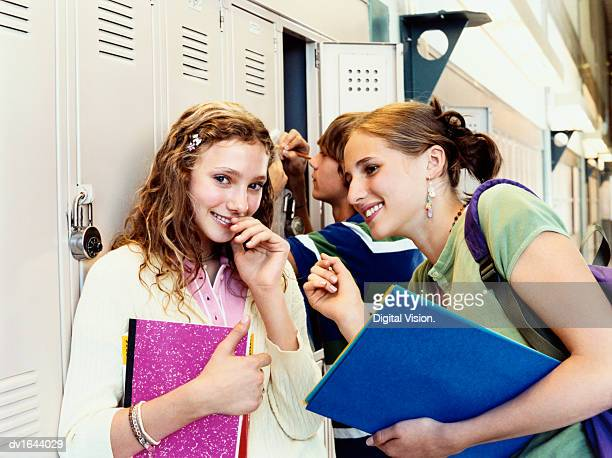teenage girls stand whispering in a corridor beside their lockers - shy stock pictures, royalty-free photos & images