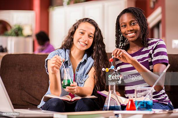 Teenage girls, students studying chemistry, science at home.