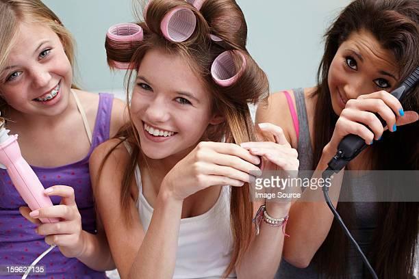 Teenage girls styling their hair