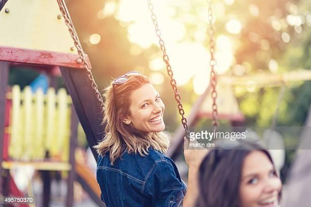 Teenage girls swinging outside