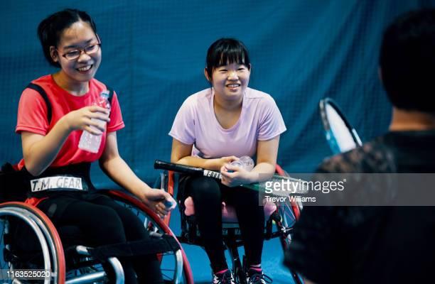 Teenage girls taking a break from playing wheelchair tennis
