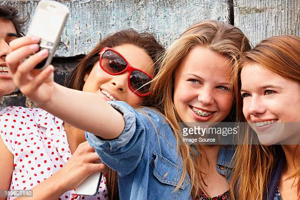 Teenage girls taking a picture of themselves on smartphone