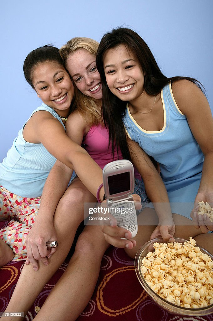 Teenage girls taking a picture with camera phone : Foto de stock