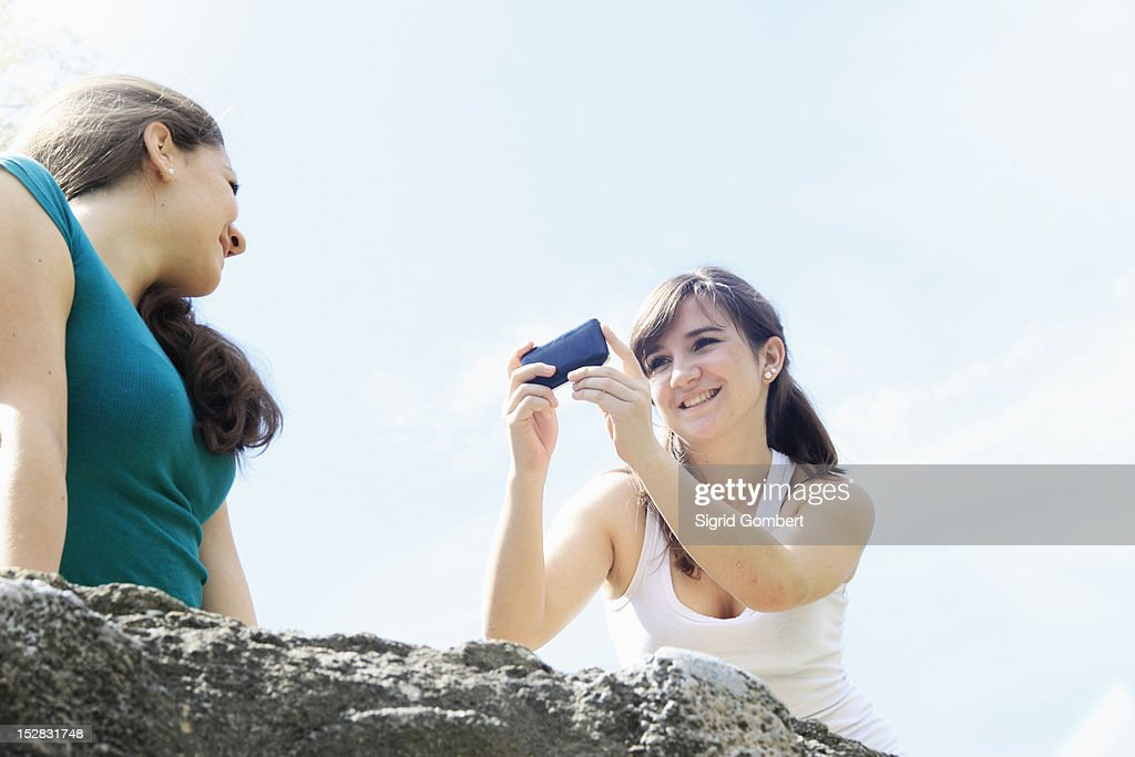 Teenage girls taking pictures outdoors : Stock-Foto