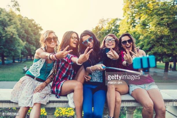 Teenage girls taking selfie in the park with selfie stick