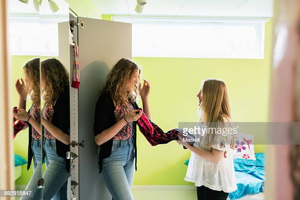 Teenage girls talking while choosing clothes from closet at home