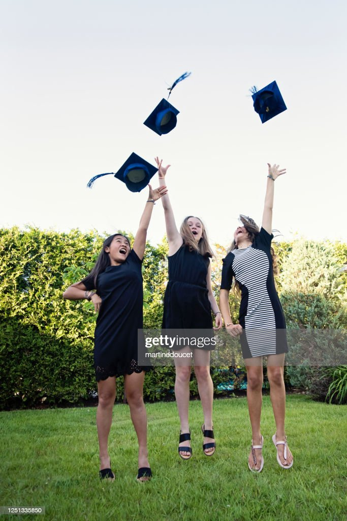 Teenage girls throwing graduation hats in backyard. : Stock Photo