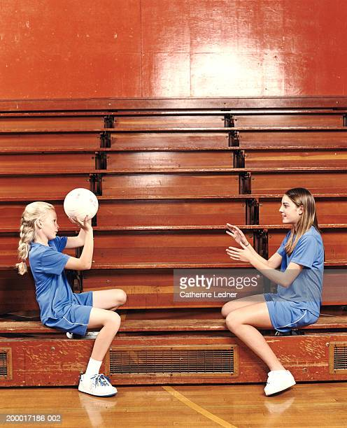 Teenage girls (14-16) tossing volleyball to each other
