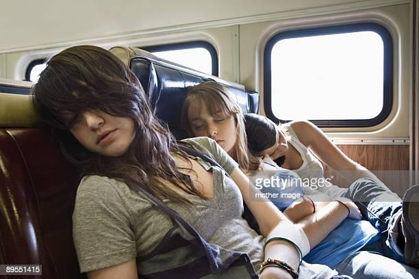 Teenage girls traveling together sleeping on train