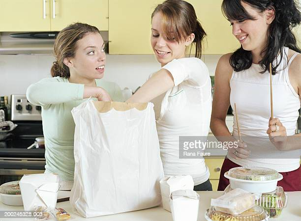 Teenage girls (17-19) unpacking chinese takeout food in kitchen