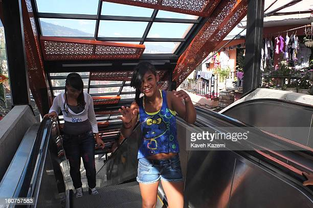 Teenage girls use the escalators in '20 de Julio' neighborhood in the Comuna 13 slums on January 5 2013 in Medellin Colombia The stairway is divided...