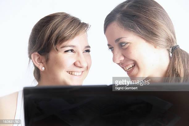 teenage girls using laptop together - sigrid gombert fotografías e imágenes de stock