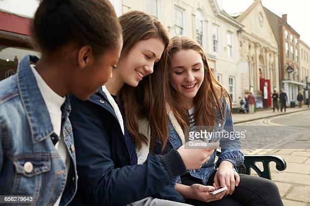 Teenage Girls Using Mobile Phones In Urban Setting
