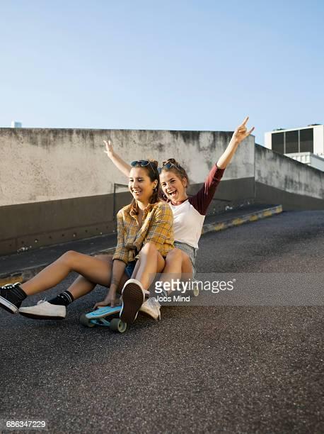 Teenage girls using skateboard on rooftop car park