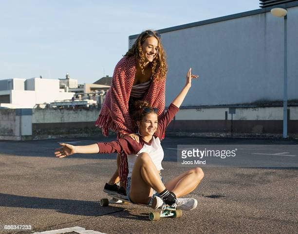 teenage girls using skateboard on rooftop car park - weiblicher teenager stock-fotos und bilder