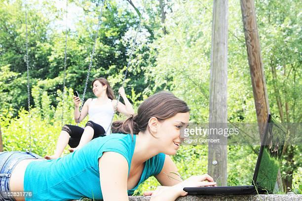 teenage girls using technology outdoors - sigrid gombert fotografías e imágenes de stock