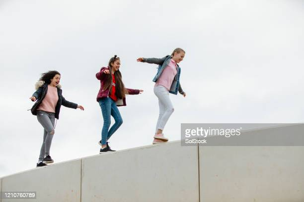 teenage girls walking along high wall - independence stock pictures, royalty-free photos & images